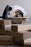 Circular saw and timber. A workshop table with circular saw and timber Royalty Free Stock Photo