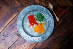 Circular silver plate with three colourful spices on it chilli t Stock Photography