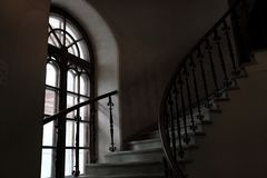 Circular spiral staircase in the tower and a tall gothic window. Dark tower royalty free stock images