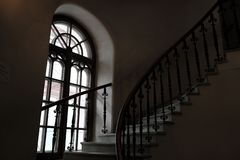 Circular spiral staircase in the tower and a tall gothic window. Dark tower royalty free stock photography