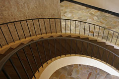 Circular staircase. Brown, capreted circular staircase with stone floor at bottom Stock Photos