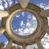 Circular structure supported by huge columns viewed on a sunny day. A beautiful and vast blue sky with puffy clouds can be seen over the structure royalty free stock photo