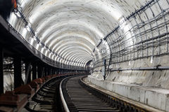 Circular tunnel subway rails and sleepers turns right and is illuminated with white light Stock Photos