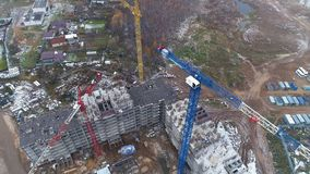 A circular view on an unfinished apartment building with several floors. A rotating view on a construction site with an unfinished building with several cranes stock video