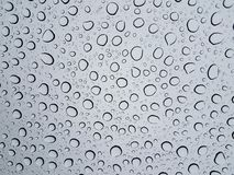 Circular water droplets or drops on glass window from rain. Circular water droplets or drops on glass window or surface from the rain royalty free stock photography