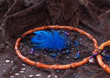 Circular woden dreamcatcher with beads and blue feather on lace royalty free stock image