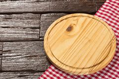Circular wooden table and checkered cloth napkin. royalty free stock photography