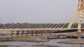 Circulation automobile sur le pont à haubans Signature en cours de construction au-dessus de la rivière Yamuna à Delhi banque de vidéos