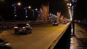 Circulation de soirée Les lumières de ville Voitures se déplaçant au-dessus du pont du sud à Riga, Lettonie banque de vidéos