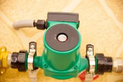 Circulation Pumps on the Background. Circulation Pumps on theof pipes of a warm floor under a laminate of a parquet and a tile Floor heating pipe. Installation Royalty Free Stock Images
