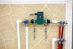 Circulation Pumps on the Background. Circulation Pumps on theof pipes of a warm floor under a laminate of a parquet and a tile Floor heating pipe. Installation Stock Image