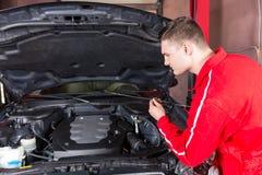 Circulez en voiture le mécanicien vérifiant le niveau d'huile dans une voiture photos stock