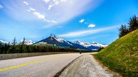 Circulez en voiture les vélos conduisant la route de lac Duffey entourée par les montagnes couvertes par neige photos libres de droits