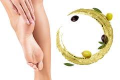 Circulez l'?claboussure d'huile d'olive pr?s des pieds femelles Concept de Skincare photo stock