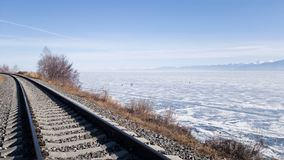 Circum-Baikal railway. The rails go away. On the right you can see lake Baikal in ice and snow and a view of the mountains. In the distance stock photos