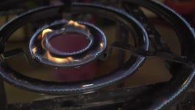 Circunde el avellanador del gas que quema el fuego y la cacerola azules en la estufa de cocina para cocinar cocinar de la comida  metrajes