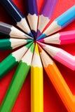 Circunde la carta de color hecha de los lápices del color en el fondo rojo Imágenes de archivo libres de regalías