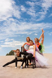 Circus acrobats vertical. A young circus troupe pose supporting one another in the desert sand Stock Image