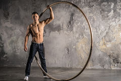 Circus artist in aCyr Wheel with strong muscles. Strong circus performer spinning a cyr wheel Stock Photography