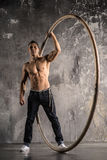Circus artist in aCyr Wheel with strong muscles. Strong circus performer spinning a cyr wheel Royalty Free Stock Photo