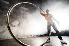 Circus artist in aCyr Wheel. Strong circus performer spinning a cyr wheel Royalty Free Stock Images