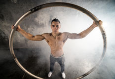Circus artist in aCyr Wheel. Strong circus performer spinning a cyr wheel Stock Image