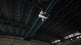 Circus artist on the aerial straps in the big deserted building stock footage