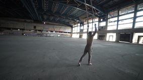 Circus artist on the aerial straps in the big deserted building stock video