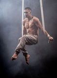 Circus artist on the aerial straps man. Circus artist on the aerial straps with Strong muscles against the background of a smoke Royalty Free Stock Image