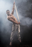 Circus artist on the aerial straps man. Circus artist on the aerial straps with Strong muscles against the background of a smoke Royalty Free Stock Images