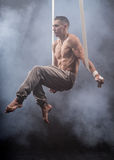 Circus artist on the aerial straps man. Circus artist on the aerial straps with Strong muscles against the background of a smoke Stock Photography