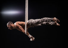 Circus artist on the aerial straps man. Circus artist on the aerial straps with Strong muscles on black background Stock Photography
