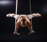 Circus artist on the aerial straps man. Circus artist on the aerial straps with Strong muscles on black background Stock Image