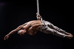Circus artist on the aerial straps man. Circus artist on the aerial straps with Strong muscles on black background Royalty Free Stock Photo