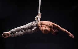 Circus artist on the aerial straps man. Circus artist on the aerial straps with Strong muscles on black background Royalty Free Stock Image