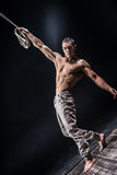 Circus artist on the aerial straps man. Circus artist on the aerial straps with Strong muscles on black background Royalty Free Stock Photography