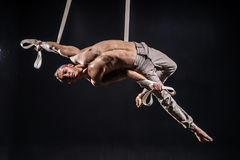 Circus artist on the aerial straps man. Circus artist on the aerial straps with Strong muscles on black background Royalty Free Stock Photos