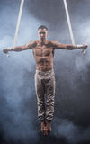 Circus artist on the aerial straps man. Circus artist on the aerial straps with Strong muscles on black background Stock Images