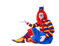 Circus Clown. Sitting circus clown holding your product in his hand Stock Photo