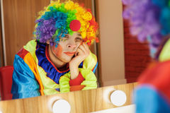 Circus clown looks in a mirror in makeup room. Stock Image