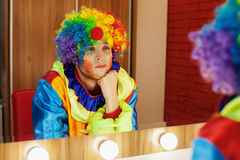 Circus clown looks in a mirror in makeup room. Circus clown looks in a mirror in a make-up room. In waiting of the entertainment Stock Photography