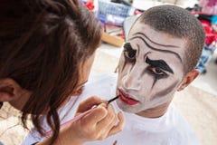 Circus Clown Makeup. Makeup artist lining lips of male circus clown Royalty Free Stock Photography