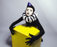 Circus fashion mime posing near a yellow square royalty free stock photography