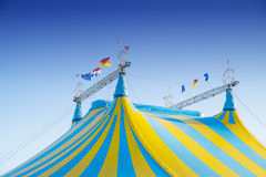 Circus international. Blue and yellow striped circus tents under a blue sky Stock Image