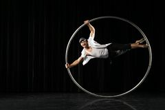 Man with circle at black background. Circus performer artist in a Cyr Wheel Roy Cyr in theatre at a black background Royalty Free Stock Photos