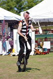 Circus Performer Juggles While Riding Unicycle. Suwanee, GA, USA - May 19, 2012:  A male circus performer juggles pins riding a unicycle while  performing for Royalty Free Stock Photos