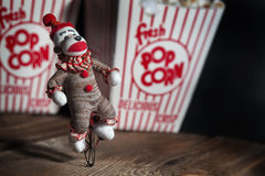 Circus Sock Monkey. A vintage sock monkey dressed as a circus performer riding a unicycle with vintage popcorn boxes blurred in background Royalty Free Stock Photos