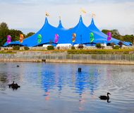 Circus style blue tent on the bank of the river Royalty Free Stock Photos