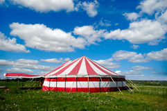 Circus tent. A red and white striped circus tent in green nature. The sky is blue with white cumulus clouds Royalty Free Stock Image