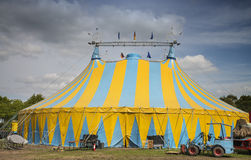 Circus tent. Blue and yellow striped circus tent under a blue cloudy sky Royalty Free Stock Photo
